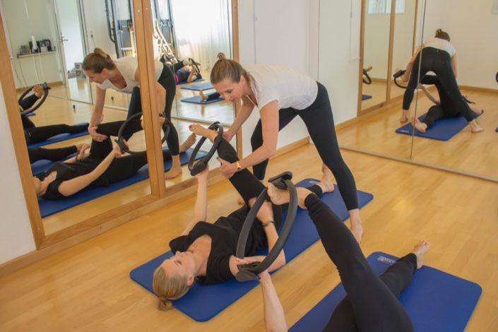 Hilfestellung bei Pilates-Übung im Gruppenkurs